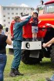 El bombero pone un casco del fuego en el muchacho que se está colocando encendido fotos de archivo libres de regalías