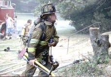 El bombero se prepara para entrar una casa ardiente fotos de archivo