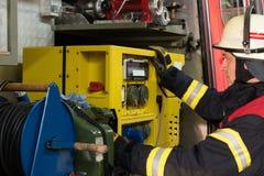 El bombero utilizó el generador de la electricidad en el coche de bomberos Foto de archivo libre de regalías