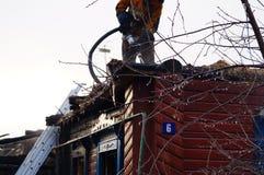 El bombero vierte el tejado de la casa de madera después de extintor Imágenes de archivo libres de regalías