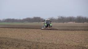 El borrachín y afloja el suelo en el campo antes de sembrar El tractor ara un campo con una paleta almacen de video