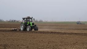 El borrachín y afloja el suelo en el campo antes de sembrar El tractor ara un campo con una paleta almacen de metraje de vídeo