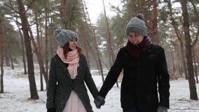 El bosque al aire libre del invierno tiró de los pares jovenes de la boda que caminaban y que se divertían que llevaba a cabo las metrajes