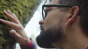 El botánico estudia la flora y mira el musgo en el árbol almacen de metraje de vídeo
