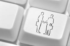 El botón con un emblema de la sacudida de la mano de dos hombres de negocios en el th Fotografía de archivo