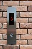 El botón del elevador abajo suela G en fondo de la textura del ladrillo Fotos de archivo libres de regalías