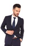 El botón joven del ` s del traje de la tenencia del hombre de negocios mira abajo Fotos de archivo libres de regalías