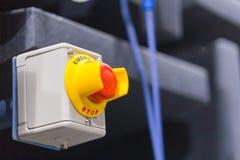El botón rojo de la emergencia o botón de paro para la prensa de la mano El botón de paro para la máquina industrial Fotografía de archivo