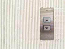 El botón superficial del elevador del primer adentro arriba y abajo de muestra de la flecha en la pared del cemento texturizó el  Fotografía de archivo