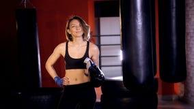 El boxeador de la muchacha está mirando en el guante de boxeo Retrato 4K almacen de metraje de vídeo