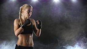 El boxeador de la muchacha hace la perforación y el retroceso con el pie Cámara lenta cercana almacen de video