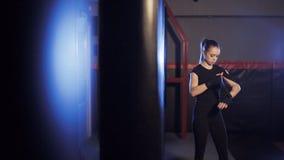 El boxeador de sexo femenino envuelve sus manos en el gimnasio del boxeo metrajes