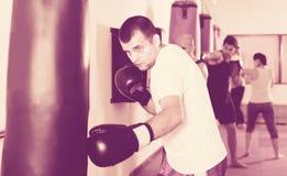 El boxeador de sexo masculino está batiendo un bolso del boxeo foto de archivo libre de regalías