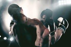 El boxeador en una competencia del boxe bate a su opositor Imagen de archivo