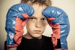 El boxeador joven sostiene la cara cerca que frunce el ceño con guantes de las manos Fotografía de archivo libre de regalías
