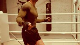 El boxeador profesional joven con el cuerpo atlético está saltando en cuerda de salto en ringside metrajes