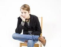 El boyt adolescente hermoso se sienta en una silla Foto de archivo