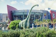 El Brachiosaurus verde sube su cuello sobre la ciudad del cine imágenes de archivo libres de regalías