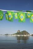 El brasileño señala la montaña Rio de Janeiro Brazil de Sugarloaf por medio de una bandera Imagenes de archivo
