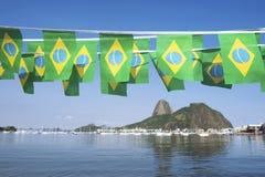 El brasileño señala la montaña Rio de Janeiro Brazil de Sugarloaf por medio de una bandera Imágenes de archivo libres de regalías