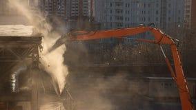 El brazo de la demolición del excavador en nube de polvo iluminada por el sol desmonta el bui Fotos de archivo libres de regalías