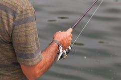 El brazo del hombre con la caña de pescar y el carrete fotos de archivo