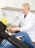 El brazo del paciente feliz del doctor Applying Bandage On después del análisis de sangre imagen de archivo