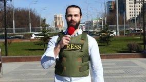 El brazo del reportero con un micr?fono que lleva un chaleco almacen de metraje de vídeo