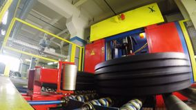 El brazo del robot toma lugares del neumático en caso pone el rollo almacen de metraje de vídeo