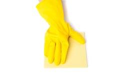 El brazo en los guantes de goma quita el polvo fotografía de archivo libre de regalías