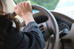 El brazo y la mano de una conducción de la mujer Fotografía de archivo