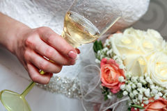 El bride& x27; s da sostener un vidrio de champán y un ramo de la boda de flores rojas y blancas Imágenes de archivo libres de regalías