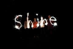 El brillo de la palabra escrito con las bengalas contra un fondo negro Fotografía de archivo