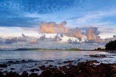 El brillo ligero de oro en la montaña con el cielo de las nubes en agua de mar perfectamente tranquilo le gusta la línea de crist Foto de archivo
