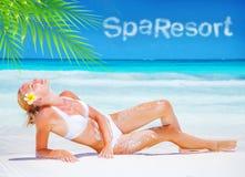 El broncear bastante femenino en la playa Imagen de archivo libre de regalías