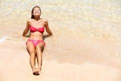 El broncear del sol de la muchacha del bikini de las vacaciones de la playa feliz imagen de archivo