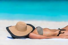 El broncear del sol el dormir de la mujer del sombrero de la relajación de la playa Foto de archivo libre de regalías