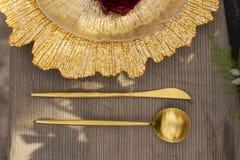 El brote de una rosa roja, mintiendo en una placa de oro y un spoo de oro Imágenes de archivo libres de regalías