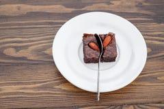 El brownie hecho en casa de la almendra del chocolate fue dividido con una cuchara Foto de archivo libre de regalías