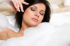 El brunette atractivo se relaja tomando un baño. Imagen de archivo libre de regalías