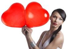 El brunette atractivo toma dos globos en forma de corazón con ambas manos Fotografía de archivo libre de regalías