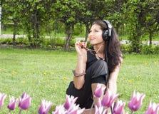 El brunette bonito sonriente se sienta en la hierba Imagen de archivo libre de regalías