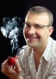 El Brunette fuma un tubo rojo y sonríe. Imagenes de archivo