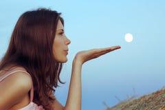 El brunette hermoso sopla la luna con la palma Fotos de archivo