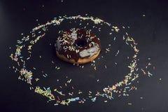 El buñuelo del chocolate en el círculo de colorido asperja, postre sabroso imagen de archivo libre de regalías