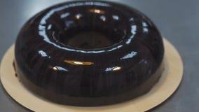 El buñuelo esmaltado se coloca en la placa plana en cocinar la tabla del metal metrajes