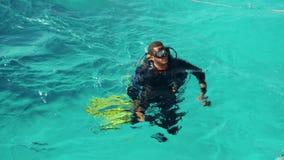 El buceador en el Mar Rojo se está preparando a la zambullida del equipo de submarinismo al filón y está nadando en el agua, Egip metrajes