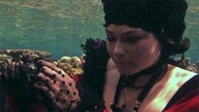 El buceador libre modelo subacuático joven en vestido rojo fotografía en cámara en el Mar Rojo almacen de metraje de vídeo