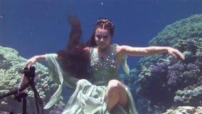 El buceador libre modelo subacuático presenta para la cámara en el fondo de corales en el Mar Rojo metrajes