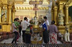 El budista vierte el agua sobre la estatua de Buda Imágenes de archivo libres de regalías